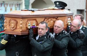 The coffin of PSNI Constable Ronan Kerr is carried through his home town of Beragh in Co Tyrone, to the Church of the Immaculate Conception by colleagues