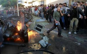 People look at a wreckage of the car in which was killed Ahmed Jabari, head of the Hamas military wing in Gaza City, Wednesday, Nov. 14, 2012. The Israeli military said its assassination of the Hamas military commander marks the beginning of an operation against Gaza militants. (AP Photo/Adel Hana)