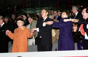01/01/2000 Queen Elizabeth II and British Prime Minister Tony Blair joins wife Cherie, singing 'Auld Lang Syne' during midnight celebrations to welcome in the new year at the Millennium Dome, London. PRESS ASSOCIATION