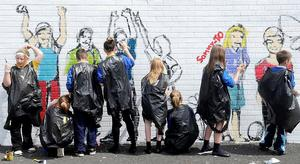 Children from a local school painting a new mural in the lower Shankill area