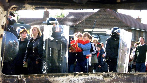 Holy Cross Primary School Protest September 2001. Riot police and army march Holy Cross school children and their parents past burnt out cars and protesting loyalists on their second day back to school in Ardoyne, North Belfast this morning.