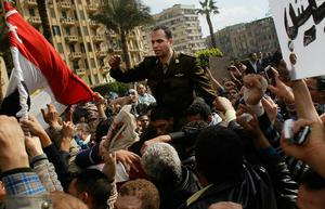 CAIRO, EGYPT - JANUARY 30:  An Egyptian Army officer sympathizing with marchers is carried during an anti-government protest in Tahrir Square January 30, 2011  in Cairo, Egypt. As President Mubarak struggles to regain control after five days of protests he has appointed Omar Suleiman as vice-president. The present death toll stands at 100 and up to 2,000 people are thought to have been injured during the clashes which started last Tuesday. Overnight it was reported that thousands of inmates from the Wadi Naturn prison had escaped and that Egyptians were forming vigilante groups in order to protect their homes after Police were nowhere to be seen on the streets.  (Photo by Chris Hondros/Getty Images)
