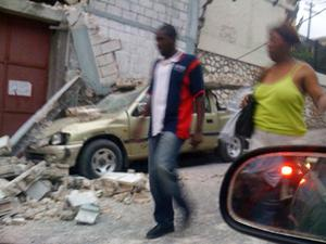 People walk past a crushed car and other rubble in Port-au-Prince on Tuesday, Jan. 12, 2010