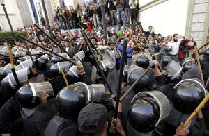 Egyptian anti-riot police confront Egyptian activist outside a journalists syndicate in downtown Cairo, Egypt, Wednesday, Jan. 26, 2011. A small gathering of Egyptian anti-government activists tried to stage a second day of protests in Cairo Wednesday in defiance of a ban on any gatherings, but police quickly moved in and used force to disperse the group. (AP Photo/Ben Curtis)