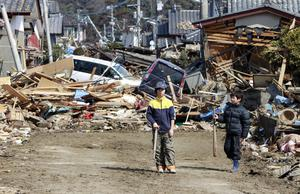 Young residents of the seaside town of Toyoma, northern Japan, walk amongst the debris around their homes Monday, March 14, 2011, three days after a giant quake and tsunami struck the country's northeastern coast. (AP Photo/Mark Baker)