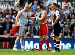 NEWCASTLE UPON TYNE, ENGLAND - APRIL 01:  Pepe Reina of Liverpool gives the goalie shirt to team mate Jose Enrique (R) after being sent off by Referee Martin Atkinson during the Barclays Premier League match between Newcastle United and Liverpool at Sports Direct Arena on April 1, 2012 in Newcastle upon Tyne, England.  (Photo by Alex Livesey/Getty Images)