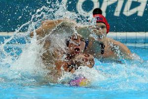 Great Britain's Joseph Regan (blue cap) battles for the ball against Romania in the mens Water Polo preliminary group B match at the Water Polo Arena, London.