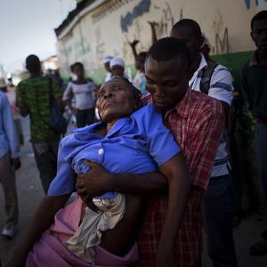A woman suffering cholera symptoms is carried to hospital in Port-au-Prince, Haiti (AP)