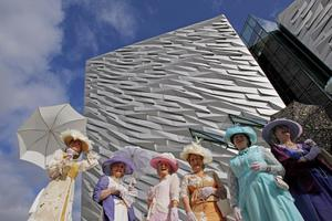 Women in period costumes outside the front of the new Titanic Belfast the world's largest Titanic-themed attraction that was officially opened today in the old shipyard at Harland and Wolff, where the doomed liner was built