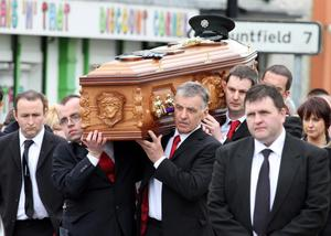 The coffin  of PSNI Constable Ronan Kerr is carried through his home town of Beragh in Co Tyrone, to the Church of the Immaculate Conception by members of the Red Knights GAA club