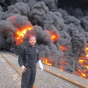 Anti-Syrian regime activist Khaled Abu-Salah stands in front of flames and smoke from a bombed pipeline in Homs (APo/Local Coordination Committees)