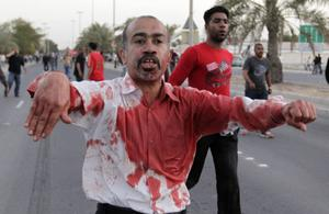 An unidentified Bahraini man reacts after he helped an anti-government protester who was injured during a demonstration in Manama, Bahrain, Friday, Feb. 18, 2011. Soldiers fired tear gas and shot heavy weapons into the air as thousands of protest marchers defied a government ban and streamed toward the landmark square that had been the symbolic center of the uprising against the Gulf nation's leaders. (AP Photo)