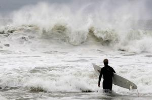 LONG BEACH, NY - OCTOBER 28:  A man surfs as Hurrican Sandy approaches on October 28, 2012 in Long Beach, New York. Sandy, which has already claimed over 50 lives in the Caribbean, is predicted to bring heavy winds and flooding to the mid-atlantic region.  (Photo by Mike Stobe/Getty Images) *** BESTPIX ***