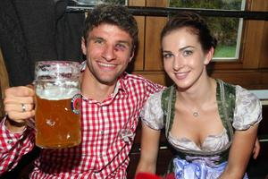 MUNICH, GERMANY - OCTOBER 07:  Thomas Mueller of FC Bayern Muenchen attends with Lisa Mueller the Oktoberfest beer festival at the Kaefer Wiesnschaenke tent on October 7, 2012 in Munich, Germany.  (Photo by Alexander Hassenstein/Bongarts/Getty Images)