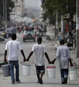 Men carry water in Port-au-Prince, Sunday, Jan. 17, 2010.