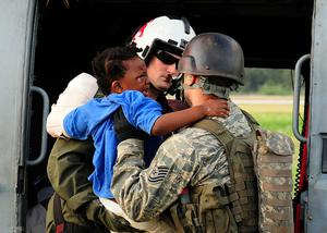 In this Saturday, Jan. 16, 2010 photo released by the U.S. Navy, Naval Air Crewman 2nd Class Jason Harold, of Goldsboro, N.C., transfers a young Haitian earthquake victim from a Seahawk helicopter during a medical evacuation in Port-au-Prince, Haiti.