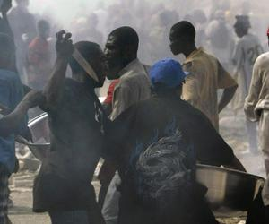 People, one holding up a knife, fight for goods taken from collapsed stores in Port-au-Prince, Haiti, Sunday, Jan. 17, 2010.