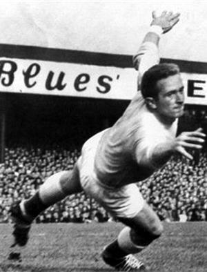 Northern Ireland and Manchester United goalkeeper, Harry Gregg, dives to save the ball during the international soccer match between Northern Ireland and Scotland at Windsor Park, Belfast, in this Oct. 3, 1959 file photo. Gregg was a reliable goalkeeper who played in 48 shutouts for Manchester United. When he climbed into the wreckage of a smashed up plane at Munich airport 50 years ago, Gregg was saving lives instead of shots.