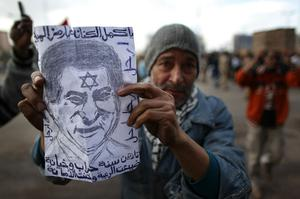 CAIRO, EGYPT - JANUARY 30:  A man in Tahrir Square holds a piece of paper with a drawing of President Hosni Mubarak  on January 30, 2011 in Cairo, Egypt. As President Mubarak struggles to regain control after five days of protests he has appointed Omar Suleiman as vice-president. The present death toll stands at 100 and up to 2,000 people are thought to have been injured during the clashes which started last Tuesday. Overnight it was reported that thousands of inmates from the Wadi Naturn prison had escaped and that Egyptians were forming vigilante groups in order to protect their homes after Police were nowhere to be seen on the streets. Broadcasts from the Al-Jazeera television network via an Egyptian satellite have now been halted.  (Photo by Peter Macdiarmid/Getty Images)