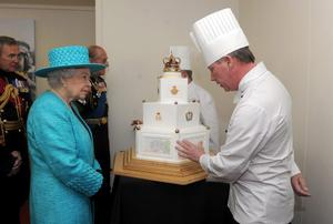 Queen Elizabeth II views a Jubilee cake made by Paul Farrant (hidden) and Mr P Roberts (right) during the Queen's Diamond Jubilee Armed Forces Parade and Muster in Windsor, Berkshire. PRESS ASSOCIATION Photo.