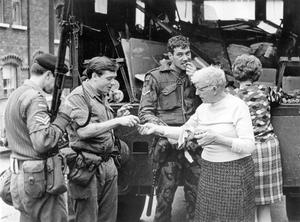 Riots. Belfast Shankill Road.  A woman hads out tea and biscuits to the troops.  27/9/1970