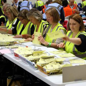 Counting agents sort through ballot papers for Avon and Somerset, at the University of the West of England in Bristol