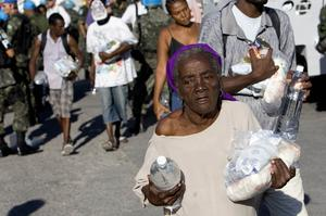 Hatians walk away with food and water distributed by Brazilian UN peacekeepers on January 22, 2010 in Port-au-Prince, Haiti