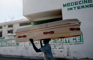 A Haitian man carries an empty coffin around in the central hospital complex January 22, 2010 in Port-au-Prince, Haiti. Aid has started trickling out to Haitians devastated by last week's earthquake that ravaged the country, though many fear not enough will reach desparate citizens in time to prevent a humanitarian catastrophe