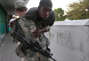 Pvt. Christopher Iker of Cincinatti, Ohio carries a Haitian man with a wounded leg through the central hospital complex January 22, 2010 in Port-au-Prince, Haiti