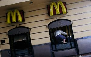 CAIRO, EGYPT - JANUARY 30:  An Egyptian man enters through the windows of a looted McDonalds restaurant just off of Tahrir Square January 30, 2011 in Cairo, Egypt. Cairo remained in a state of flux and marchers continued to protest in the streets and defy curfew, demanding the resignation of Egyptian president Hosni Mubarek. As President Mubarak struggles to regain control after five days of protests he has appointed Omar Suleiman as vice-president. The present death toll stands at 100 and up to 2,000 people are thought to have been injured during the clashes which started last Tuesday. Overnight it was reported that thousands of inmates from the Wadi Naturn prison had escaped and that Egyptians were forming vigilante groups in order to protect their homes.   (Photo by Chris Hondros/Getty Images)