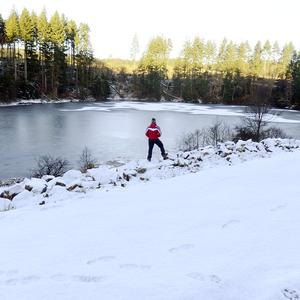 A walker looks at ice as he stands in the snow at Kielder Water, Northumberland