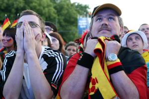 BERLIN, GERMANY - JUNE 09:  German team fans watch the Germany versus Portugal UEFA Champions League soccer match broadcast from Lviv, Ukraine on a giant outdoor screen near the Brandenburg Gate on June 9, 2012 in Berlin, Germany. The 2012 UEFA European Football Championship, also known as Euro 2012, is a 16-team tournament that Poland is co-hosting with Ukraine. Germany beat Portugal 1-0.  (Photo by Adam Berry/Getty Images)