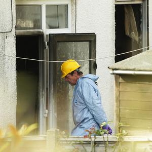 Forensic police enter the property to examine the cause of the tragedy