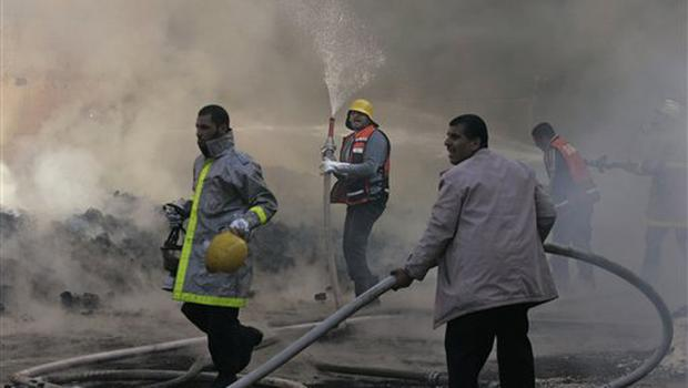 "United Nations workers and Palestinian firefighters work to try and put out a fire and save bags of food aid at the United Nations headquarters after it was hit in Israeli bombardment in Gaza City, Thursday, Jan. 15, 2009. Israeli forces shelled the United Nations headquarters in the Gaza Strip on Thursday, setting the compound on fire as U.N. chief Ban Ki-moon was in the area on a mission to end Israel's devastating offensive against the territory's Hamas rulers. Ban expressed ""outrage"" over the incident.(AP Photo/Hatem Moussa)"