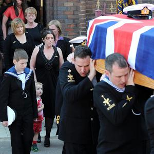 The coffin of Lieutenant Commander Ian Molyneux is followed by wife Gillian and sons Arron, left, and Charlie (PA)