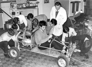 """Pupils maintenance class at work on """"Team Kilpatrick 1"""" the first car that the class/have made themselves, out of motor scooter parts. The car, as yet unfinished, is named after their teacher Mr. James Kilpatrick (standing) and will be completed with an aluminium sports body, 1969."""