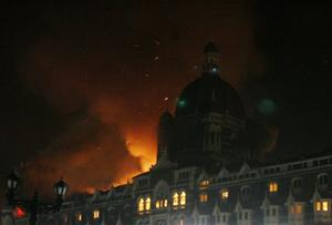 Fire engulfs a part of the Taj Hotel in Mumbai, India, Thursday, Nov. 27, 2008. Teams of heavily armed gunmen stormed luxury hotels, a popular restaurant, hospitals and a crowded train station in coordinated attacks across India's financial capital Wednesday night, killing at least 78 people and taking Westerners hostage, police said. (AP Photo/Gautam Singh)