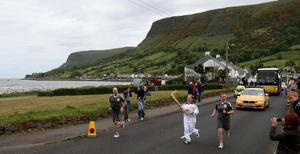 Gabrielle Cardwell carrying the Olympic Flame on the Torch Relay leg between Ballygalley and Glenariff