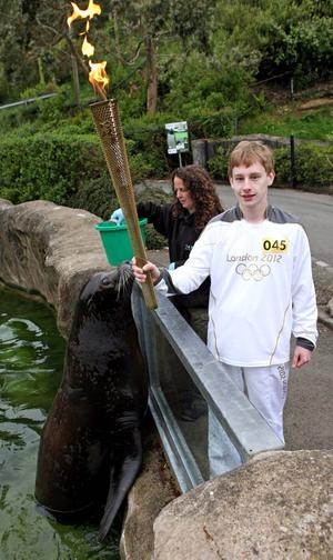 Michael Rea carries the Olympic Flame at Belfast Zoo on the Torch Relay leg between Newtownabbey and Carrickfergus