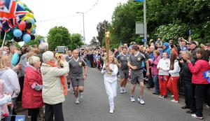 People of Castlereagh line the streets to cheer on 14-year-old Brooke Andrews as she carries the Olympic torch through Dundonald