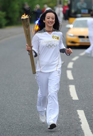 Dempsey Andrews carries the Olympic Flame on the Torch Relay leg between Newtownards and Stormont