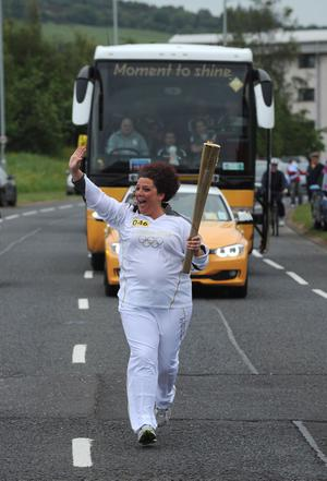 Carolynn McCord carries the Olympic Flame on the Torch Relay leg between Newtownabbey and Carrickfergus