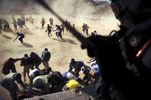 In this Jan. 17, 2010 photo released by the U.S. Navy, an air crewman drops humanitarian aid in support of earthquake relief efforts in Port-au-Prince, Haiti.  (AP Photo/U.S. Navy, Justin Stumberg)