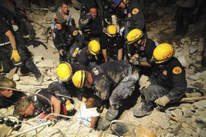 In this Jan. 17, 2010 photo released by the U.S. Navy, members of the Los Angeles County Fire Department Search and Rescue Team rescue a Haitian woman from a collapsed building in downtown Port-au-Prince, Haiti.  (AP Photo/U.S. Navy, Justin Stumberg)