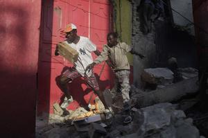 People run with goods taken from stores that collapsed during last week's earthquake in the market area of Port-au-Prince, Haiti, Monday, Jan. 18, 2010. Looting spread to more parts of downtown as hundreds of people clambered up broken walls to break into shops and take whatever they can find.  (AP Photo/Ariana Cubillos)