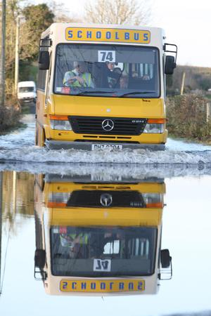 A school bus from Killyhommon Primary School, Co Fermanagh, makes its way through a flooded road