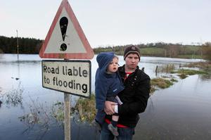 Chris McHugh with his son Jacob aged 14 months, on the flooded Samsonagh road near his home in Co Fermanagh