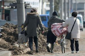 SENDAI, JAPAN - MARCH 14:  Local residents walk through an area damaged by a tsunami after a 9.0 magnitude strong earthquake struck on March 11 off the coast of north-eastern Japan, on March 14, 2011 in Sendai, Japan. The quake struck offshore at 2:46pm local time, triggering a tsunami wave of up to 10 metres which engulfed large parts of north-eastern Japan. The death toll is currently unknown, with fears that the current hundreds dead may well run into thousands.  (Photo by Kiyoshi Ota/Getty Images)