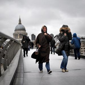 Two women hold onto their hoods while crossing London's Millennium Bridge in heavy rain and strong winds