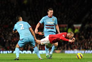 West Ham United's Winston Reid (left) tackles Manchester United's Wayne Rooney (centre) during the Barclays Premier League match at Old Trafford